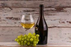 Olika slag av ost, druvor och två exponeringsglas av det vita vinet Arkivbild