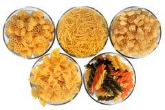 Olika slag av pasta i glass bunkar som isoleras på vit arkivbild