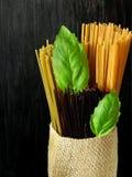 Olika slag av spagetti dekorerade med basilikasidor Arkivbild