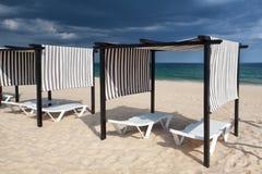 Olika slags solskydd och soldagdrivare på den tomma stranden Arkivbilder