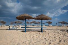 Olika slags solskydd och soldagdrivare på den tomma stranden Royaltyfri Bild