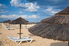 Olika slags solskydd och soldagdrivare på den tomma stranden på Tavira Arkivbilder