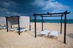 Olika slags solskydd och soldagdrivare på den tomma stranden på Tavira Royaltyfria Bilder
