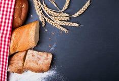Olika sorter av bröd, vete och mjöl på den svarta backgrounen Fotografering för Bildbyråer