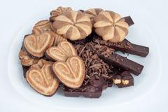 Olika sorter av choklad och kex ligger på en vit platta Royaltyfri Foto