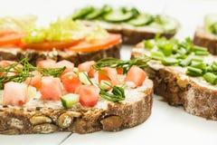 Olika sorter av färgrika smörgåsar på en vit träbakgrund Den sunda livsstilen och bantar arkivfoto