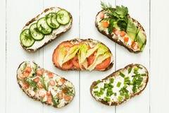 Olika sorter av färgrika smörgåsar på vit träbakgrund från ovannämnd bästa sikt Partistartknapp eller aptitretare - lägenheten lä arkivfoto