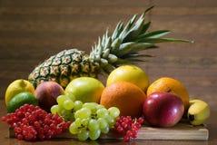 Olika sorter av frukter på träbrädet på tabellen med brun bakgrund royaltyfria foton