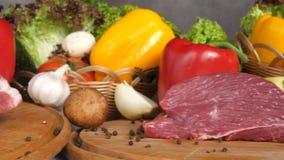 Olika sorter av kött ligger på träbräden på bakgrunden av grönsaker, grönsallat lämnar, kryddor, curry, paprika lager videofilmer