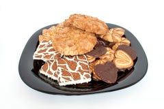 Olika sorter av läckra kakor ligger på en svart platta Arkivfoton