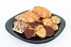Olika sorter av läckra kakor på en stor svart platta Royaltyfri Foto