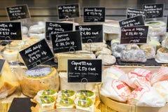 Olika sorter av ost med prislappar på marknaden i Florence, Italien Royaltyfria Bilder