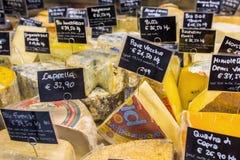 Olika sorter av ost med prislappar på marknaden i Florence, Italien Arkivfoton
