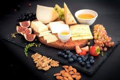 olika sorter av ostar, honung, fikonträd, muttrar, druvor och frukt på en tabell Selektivt fokusera kopiera avstånd royaltyfria bilder