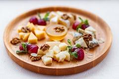 Olika sorter av ostar på träuppläggningsfatet arkivbild