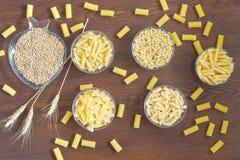 Olika sorter av pasta i glass plattor Korn av vete Arkivfoton