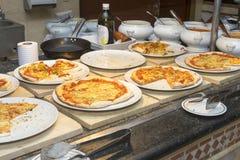 Olika sorter av pizza på vita plattor på en buffé Royaltyfri Bild