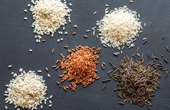 Olika sorter av ris på den mörka bakgrunden Arkivfoto