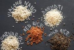 Olika sorter av ris på den mörka bakgrunden Arkivbild