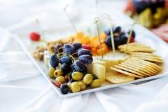 Olika sorter av vinmellanmål: ostar, smällare, frukter och oliv på den vita tabellen arkivbilder