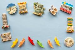 Olika souvenirmagneter och pappersskepp som är ordnade på den blåa bakgrunden Fotografering för Bildbyråer