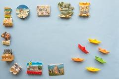 Olika souvenirmagneter och pappersskepp som är ordnade på den blåa bakgrunden Royaltyfria Bilder