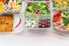 Olika sunda salladbunkar i den plast- packen för bantar lunch på vit träbakgrund Arkivbild