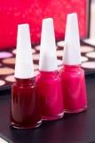 Olika tre spikar polermedelfärger och en röd, rosa färger och ljus sminkbakgrund - - rosa färger Arkivbild