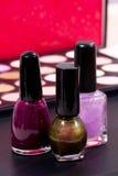 Olika tre spikar polermedelfärger och en sminkbakgrund - rosa färg, mörk rosa färg och shimmery gräsplan Royaltyfri Foto
