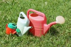 Olika tre storleksanpassade att bevattna kan ligga på gräset Royaltyfria Bilder