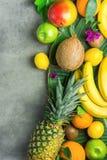 Olika tropiska sommarfrukter Äpplen Kiwi Bananas för citroner för apelsiner för ananasmangokokosnöt citrusa på mörk stenbakgrund Royaltyfri Bild