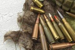 Olika typer av ammunitionar på en kamouflagebakgrund att förbereda sig kriger Royaltyfria Bilder