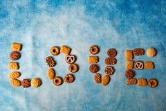 Olika typer av bisquits som bildar förälskelseord royaltyfri fotografi