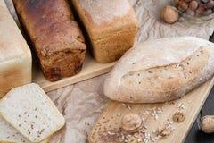 Olika typer av bröd från bagerit, lögn på ett träekbräde Runt om valnötter och hasselnötter arkivfoto