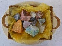 Olika typer av den naturliga rå stenen marmorerar i en presentabel korg på den tunna genomskinliga torkduken Royaltyfri Fotografi