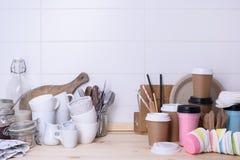 Olika typer av drinkware, keramiskt och pappers-, på trälunchräknare, vit bakgrund Fotografering för Bildbyråer