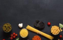Olika typer av italiensk pasta med grönsaker på den mörka svart tavlan Fotografering för Bildbyråer
