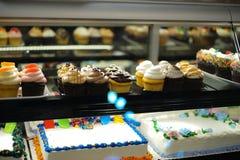 Olika typer av kakor i bakelse shoppar glass skärm royaltyfri bild