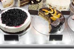 Olika typer av kakor i bakelse shoppar glass skärm arkivfoton