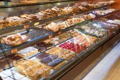 Olika typer av läckra kakor i bakelse shoppar ställer ut arkivbilder
