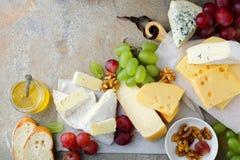 Olika typer av nya ostar med druvor, honung, bröd och valnötter kritiserar på bakgrund Royaltyfria Bilder
