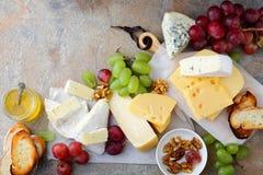 Olika typer av nya ostar med druvor, honung, bröd och valnötter på kritiserabakgrunden Arkivbild