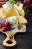 Olika typer av nya ostar på skärbräda Arkivbild