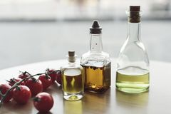 Olika typer av olja i flaskor och nya körsbärsröda tomater Royaltyfri Fotografi