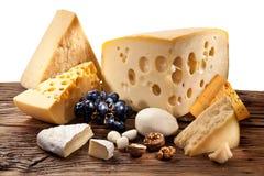 Olika typer av ost över den gamla trätabellen. Arkivbild