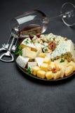 Olika typer av ost i mörk platta Arkivbild