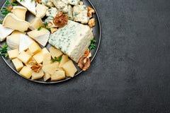 Olika typer av ost i mörk platta Arkivfoto