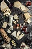 Olika typer av ost med olika kryddor, vinexponeringsglas och brödskivor på den tomma utrymmebakgrunden Royaltyfri Fotografi