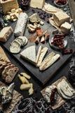 Olika typer av ost med olika kryddor, vinexponeringsglas och brödskivor på den tomma utrymmebakgrunden Royaltyfri Bild