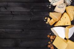 Olika typer av ost på den svarta trätabellen Top beskådar kopiera avstånd royaltyfri bild